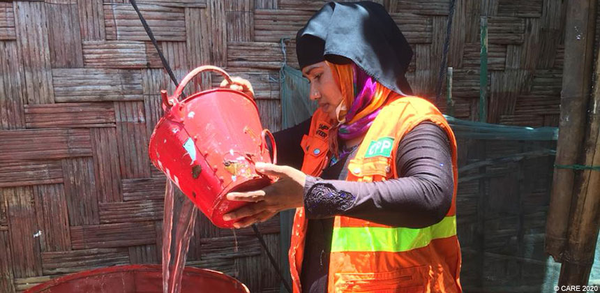 Delder Begum pouring water into an oil drum, Bangladesh