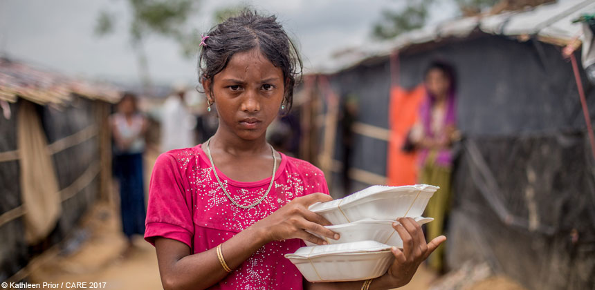 Girl holding food boxes in Bangladesh refugee camp