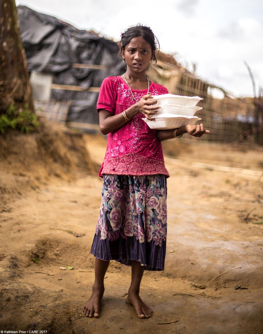 Roida holding cooked food boxes at Bangladesh refugee camp