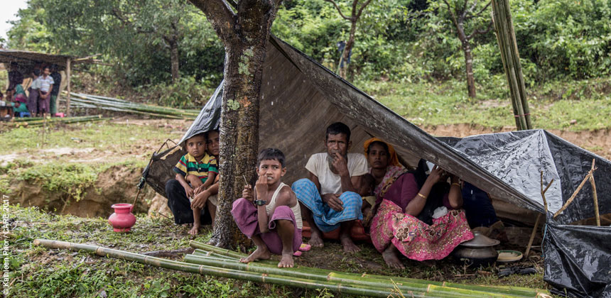 Rohingya refugee family sheltering under a plastic sheet