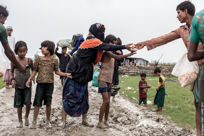 People giving food to refugees walking along a muddy path