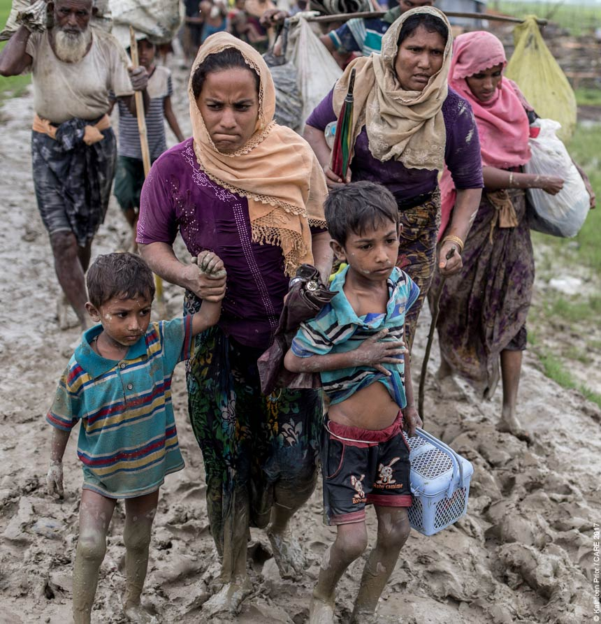 Rohingya refugees walking through mud