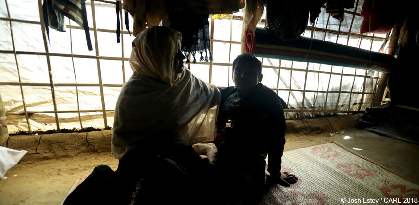 Woman and boy in silhouette inside tent at refugee camp