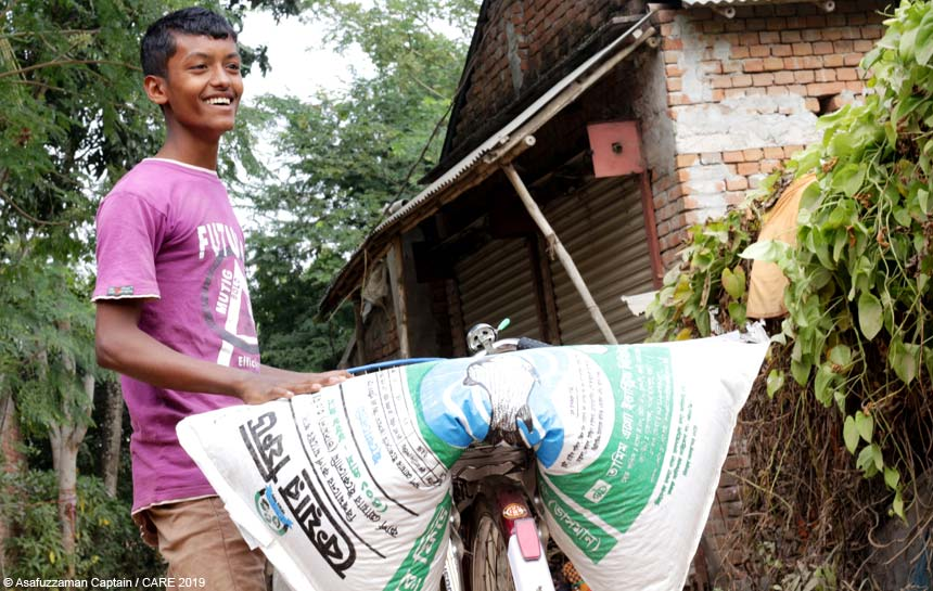 Young man with agricultural feed sack on bicycle