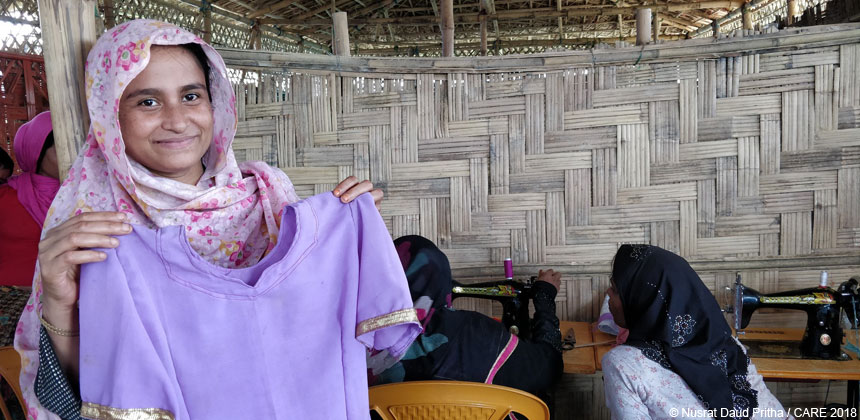 Noor Hasina holding a garment that she made in Bangladesh refugee camp