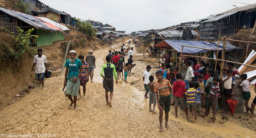 People on a muddy path at the refugee camp