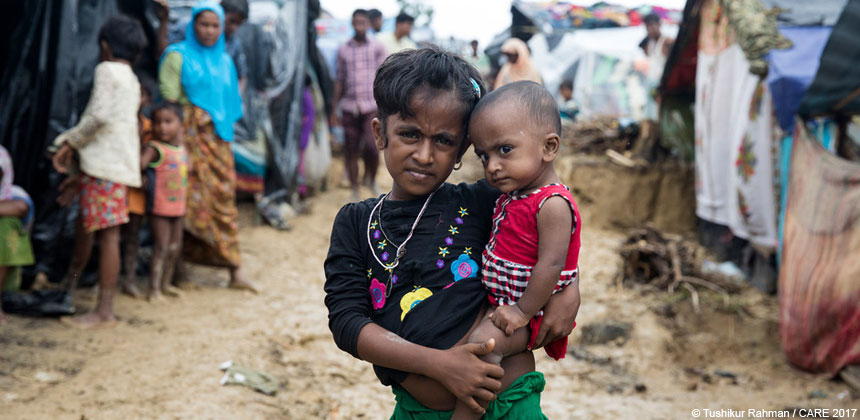 Girl holding her baby sister in Bangladesh refugee camp