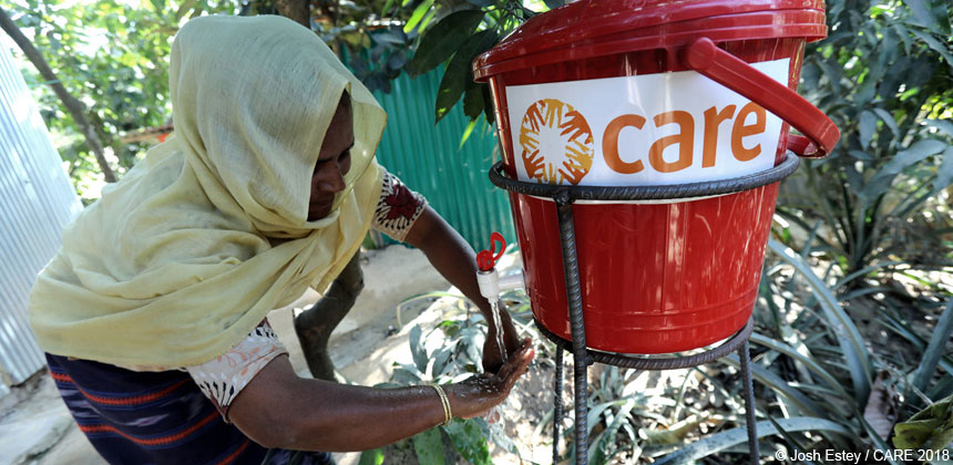 Woman washing hands from CARE bucket at refugee camp