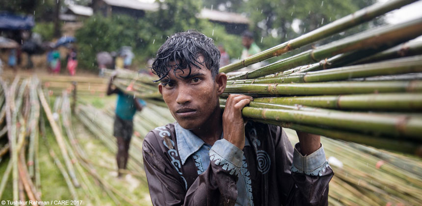 Young man carrying bamboo poles