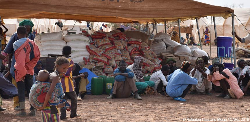 People waiting in front of sacks of food at an IDP camp in Burkina Faso