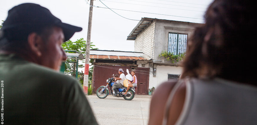 People watch from the roadside as a motorbike goes past