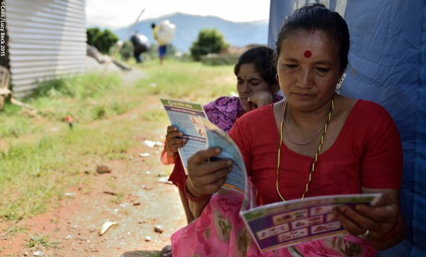 Women read brouchures on water, sanitation and hygiene after a training given by CARE after the Nepal earthquakes of April and May 2015.