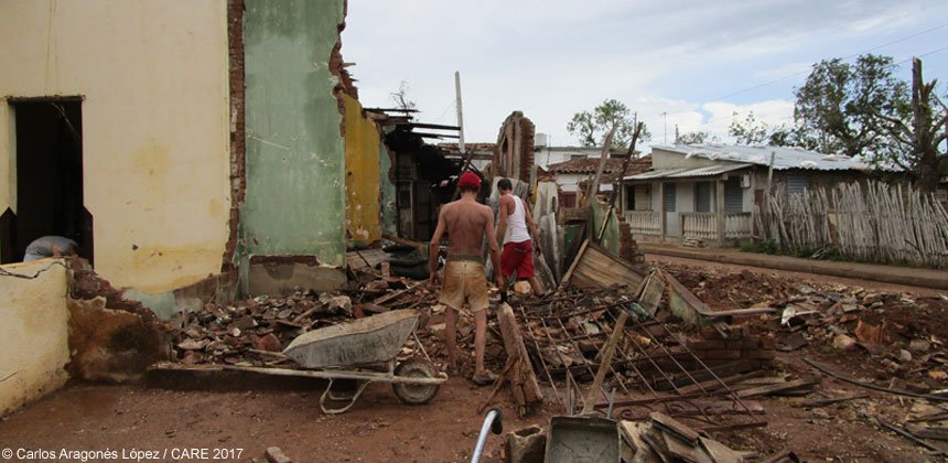 People standing in rubble from damaged houses