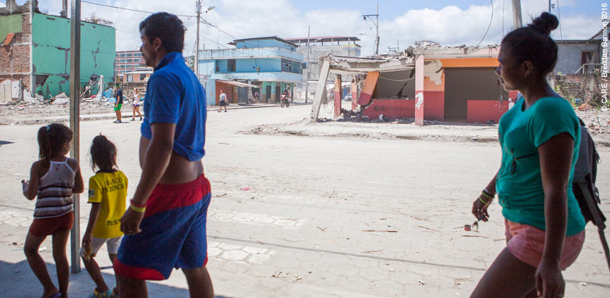 A family walking down an earthquake-damaged street