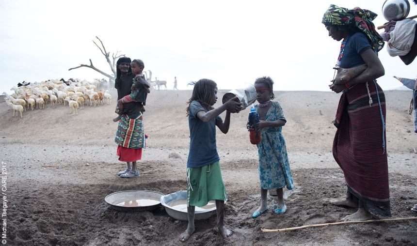 People collecting water from hole in riverbed in Ethiopia