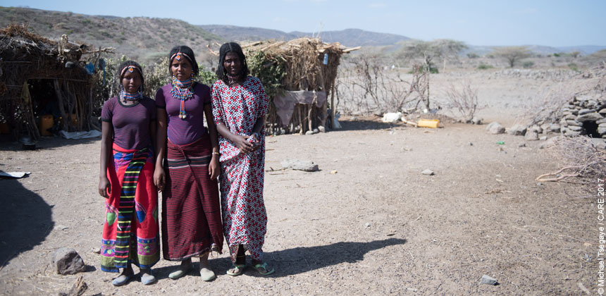Three girls standing outside homes in Bilu, Ethiopia