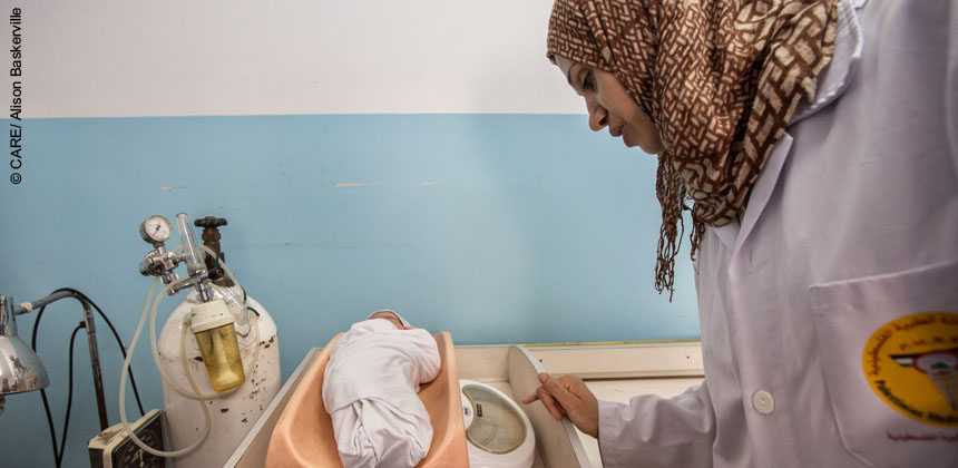 Staff Nurse Arenda Madoun, checks over a two-week-old baby in a medical centre in Jabalaya, Gaza, during the conflict in 2014