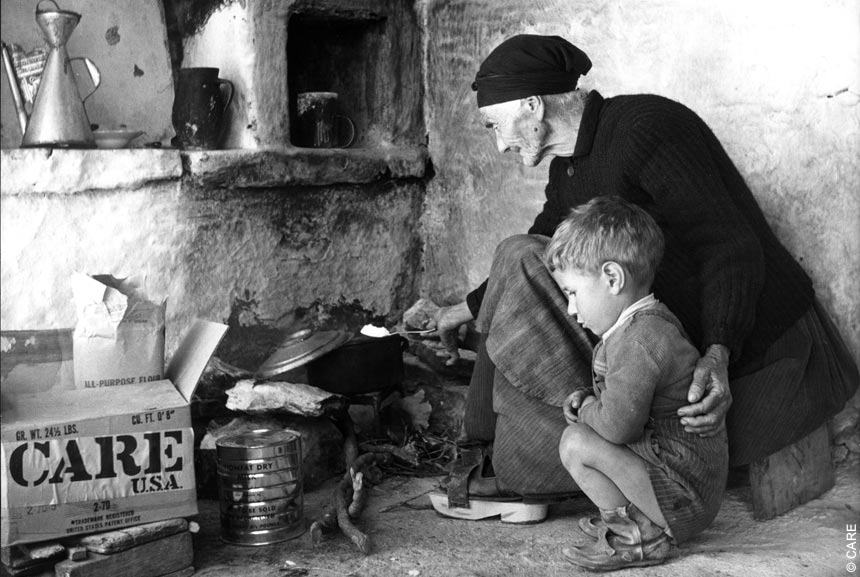 An elderly woman cooking for a boy in Greece, 1958