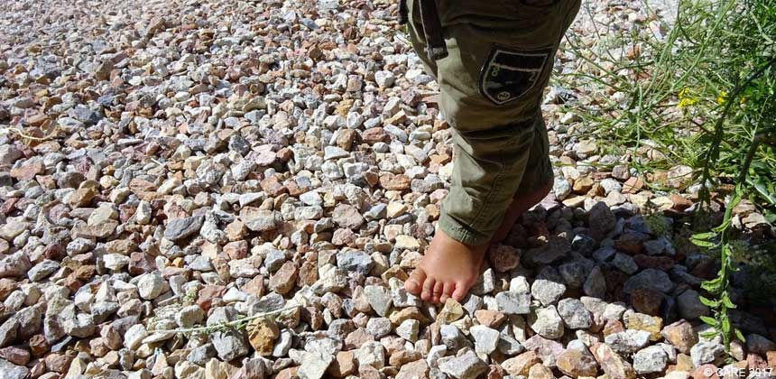A barefooted child plays on stones