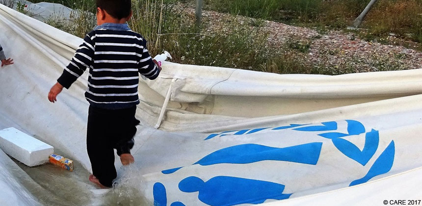 A child playing on a tarpaulin at a refugee camp