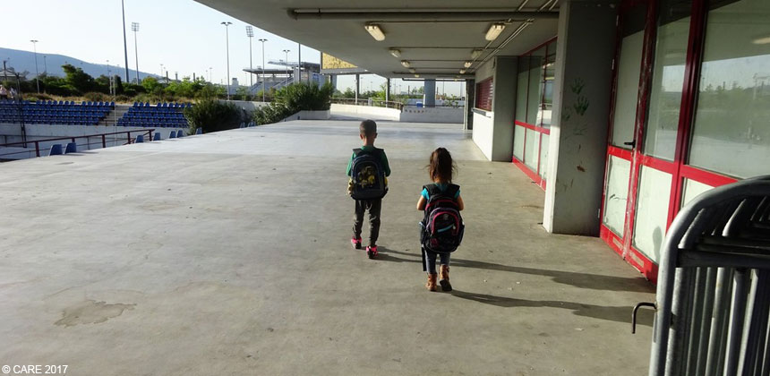 Two children walking through a stadium