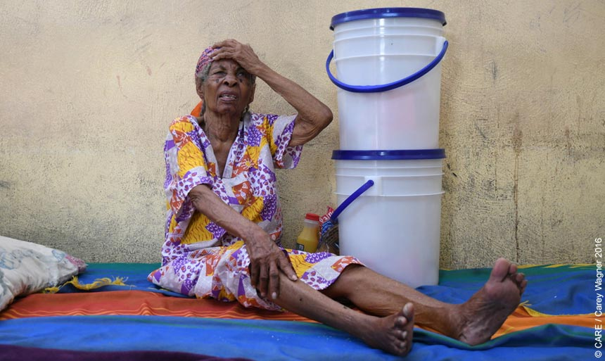 An old woman with buckets containing hygiene kits