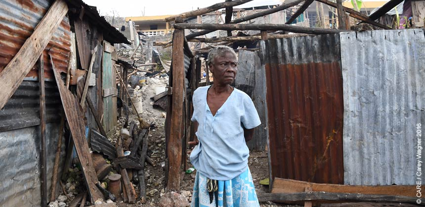Woman outside storm-damaged house