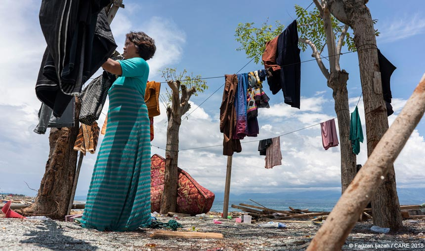 Woman in Indonesia drying clothes on a beach