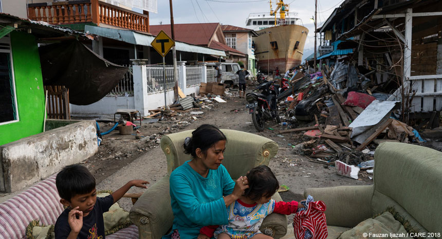 A woman and her children in a tsunami-damaged street