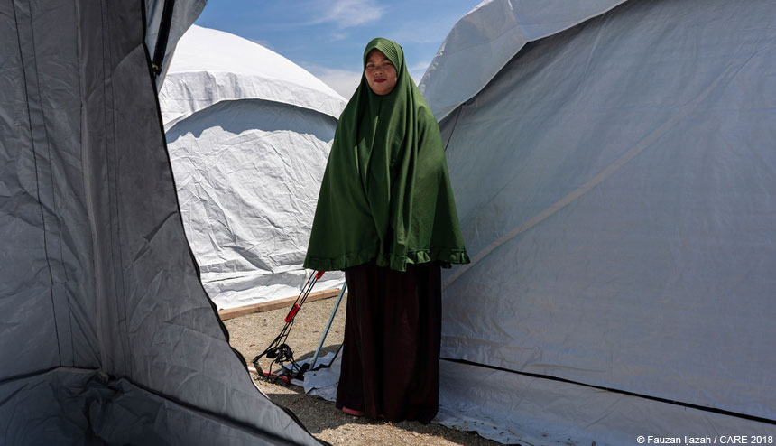 Woman standing between tents in emergency settlement