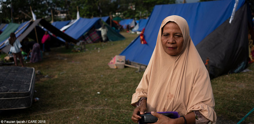 Woman standing in front of tents after Indonesia earthquake