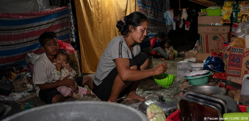 A family cooking inside their temporary shelter in Donggala