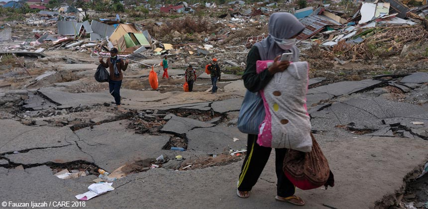 People carry belongings across earthquake-damaged road