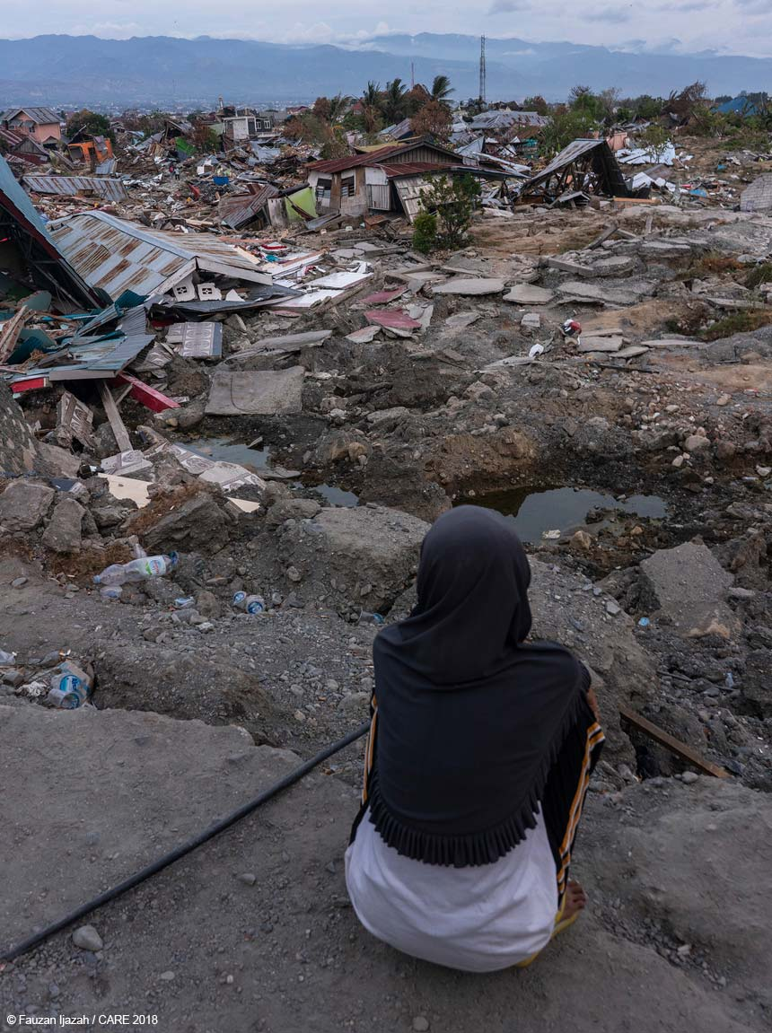 Woman looking out over area of damaged buildings