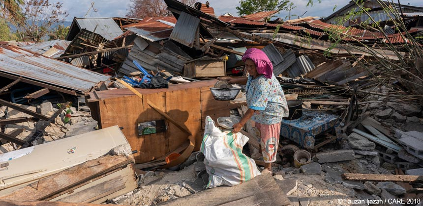 Woman salvaging belongings from damaged buildings
