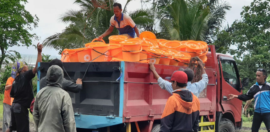 Unloading buckets from lorry in Indonesia