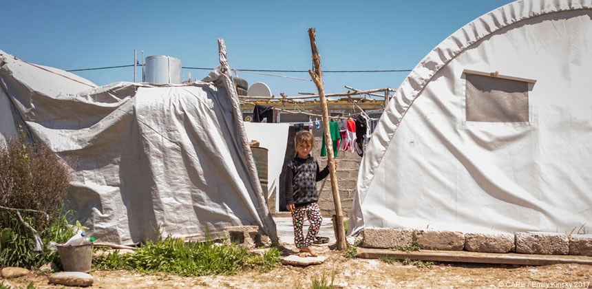 A child stands beside tents at Chamisku camp, Iraq
