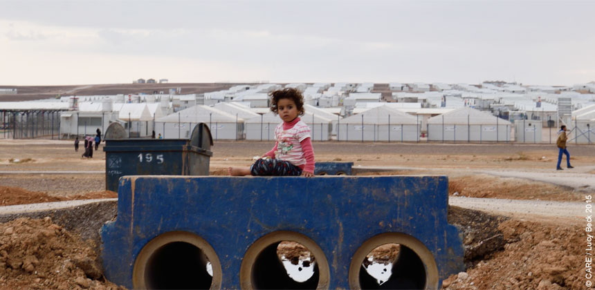 A girl sits on a drainage bridge in Azraq refugee camp, Jordan