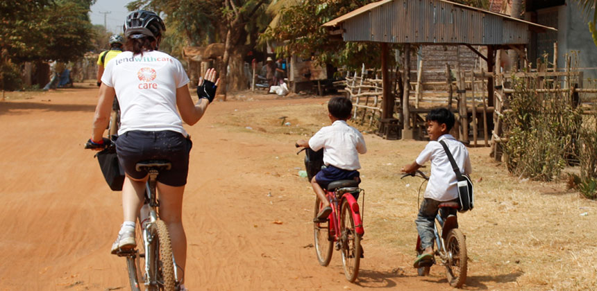 Care participant cycling in Cambodia with children cycling alongside