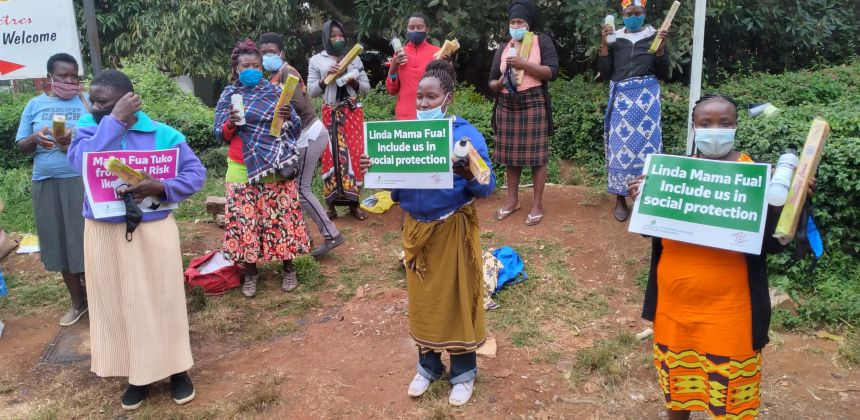 Domestic workers on streetside in Kenya holding signs