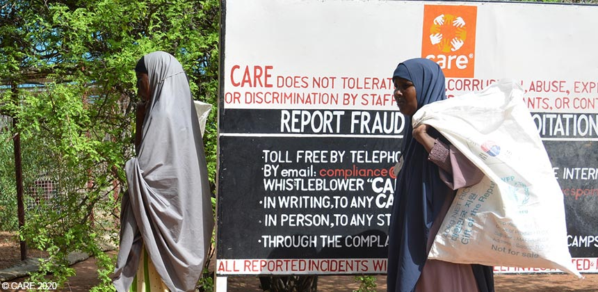 Two women queuing in front of a CARE signboard, Kenya