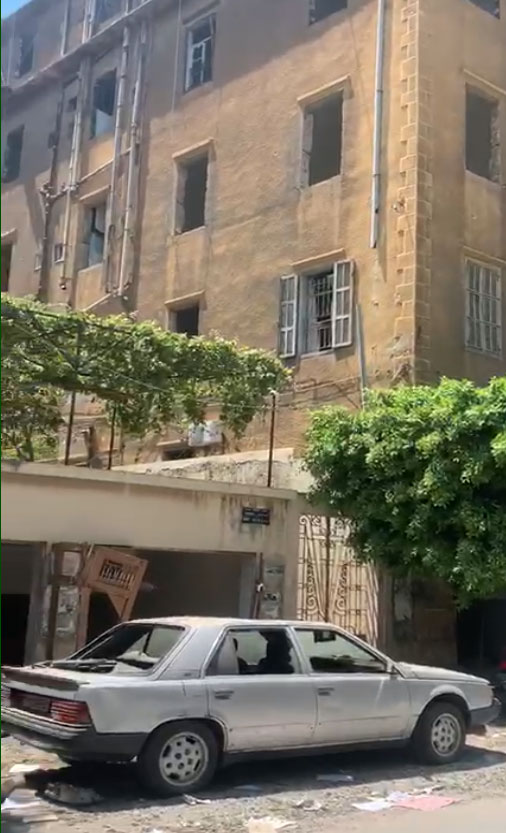 Damaged building and car in a street in Beirut
