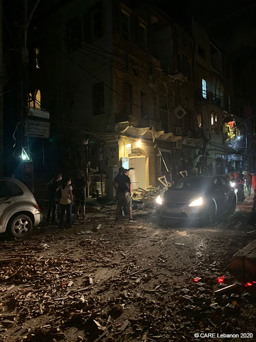 People survey the damage on a Beirut street at night