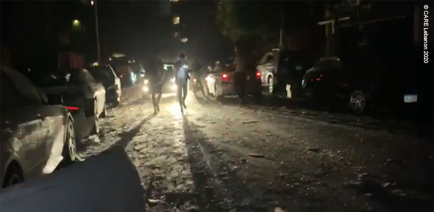 People walk through debris from the explosion, on a Beirut street at night