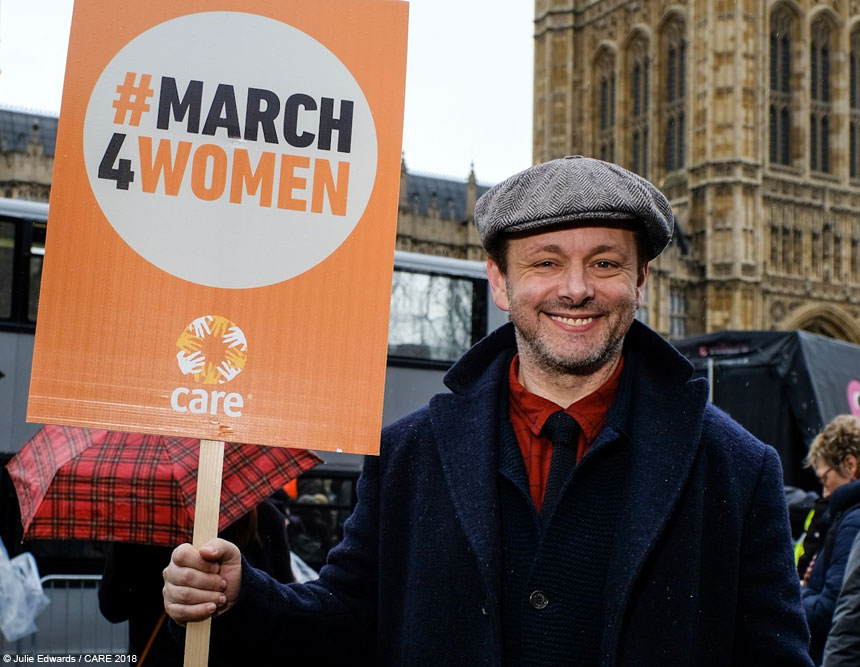 Michael Sheen holds a #March4Women placard