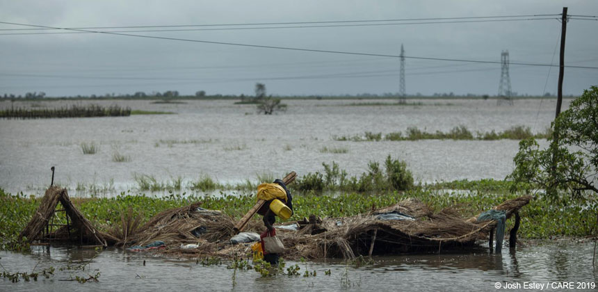 Woman wading through flood water with belongings, Mozambique
