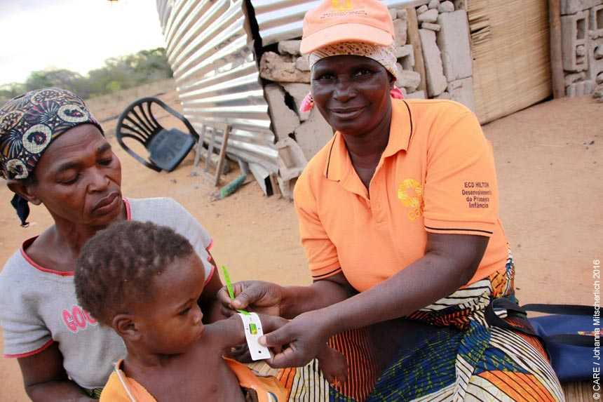 Joaquina measuring a child's arm for signs of malnutrition