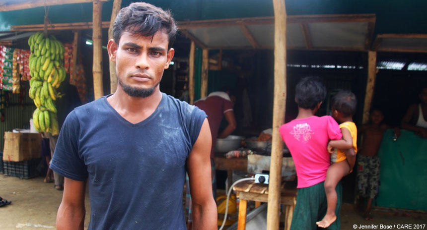 Man standing outside food stall in refugee camp in Bangladesh