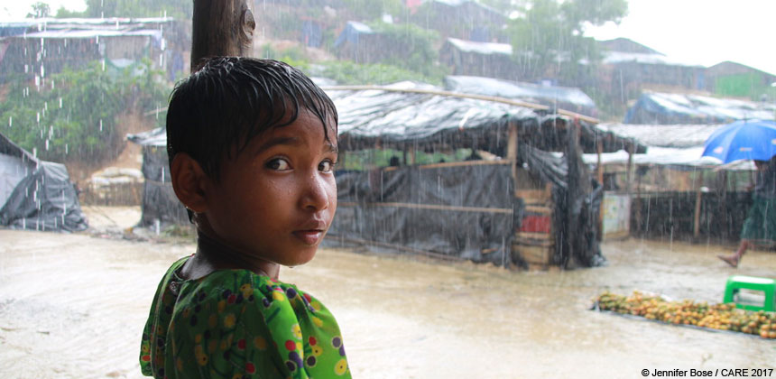 Girl sheltering from rain at refugee camp