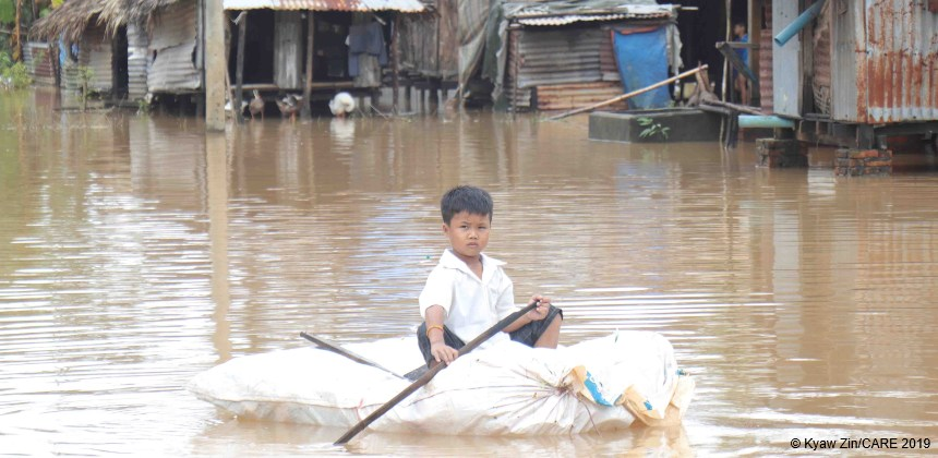 Boy on a raft beside houses after floods in Myanmar
